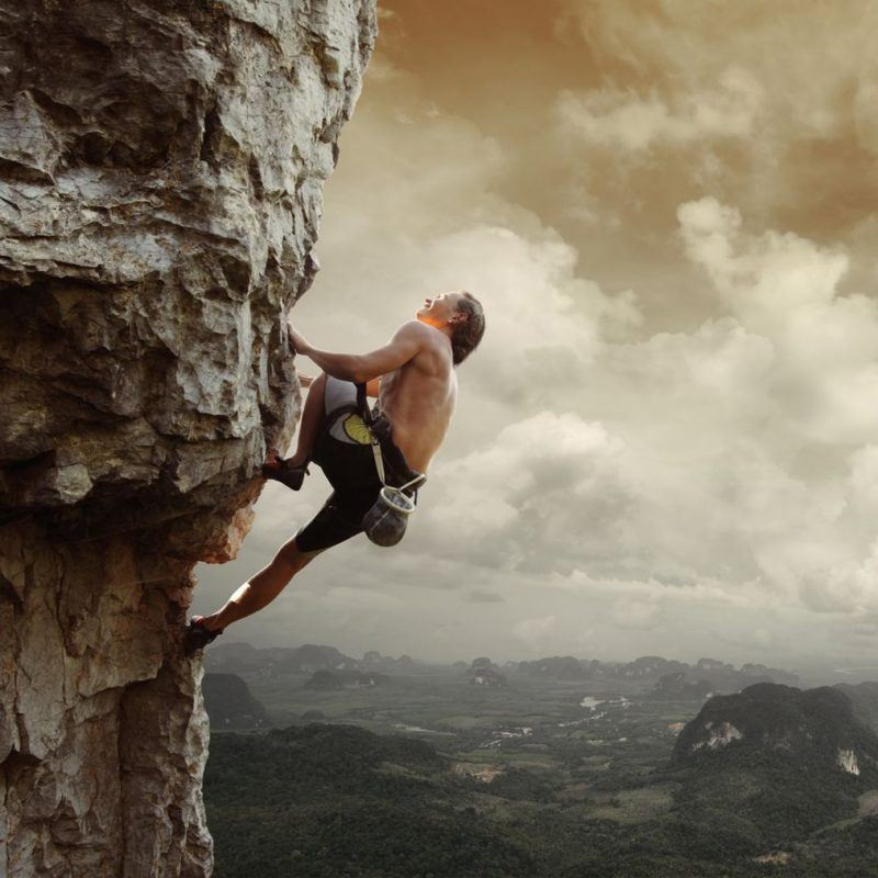 19362576 - young man climbing natural rocky wall with tropical valley on the background